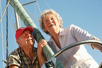 Senior couple on boat, standing by mast, low angle view