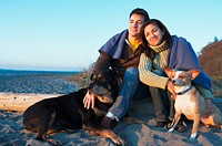 Couple sitting on beach with dogs, smiling