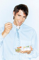 Young businessman eating sushi, smiling, portrait