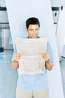 Man standing by pillar in office lobby, reading newspaper, smiling