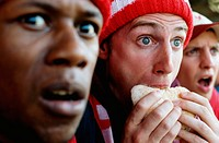Football supporters at match, one holding hambuger, close-up