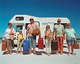 Three generational family standing outside campervan, portrait