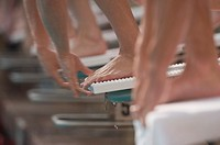 Swimmers on starting blocks before race, low section