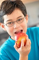 Boy (9-11) eating apple, portrait