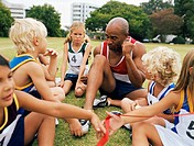 Sports teacher coaching children (4-11) sitting together on field