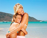 Mother and daughter (8-10) embracing on beach, smiling