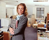 Woman holding folder in office, portrait