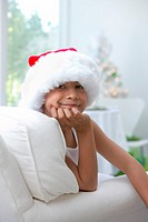 Boy (8-10) wearing Santa hat, resting chin on hand, portrait