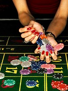 Gambling chips cascading from woman´s hands, close-up