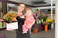 Florist worker holding toddler girl at store front, smiling, portrait