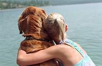 Girl (9-11) hugging dog beside lake, rear view