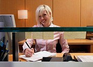 Young female receptionist taking notes, smiling, portrait