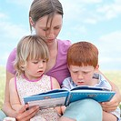 Mother reading to son and daughter (2-5) outdoors