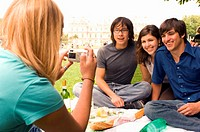 Woman photographing three young adults having picnic in park