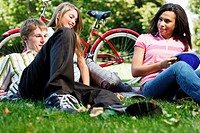 Young man, woman and teenage girl sitting in grass with flying disc