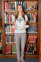 Young woman in front of library bookshelf, holding book, portrait