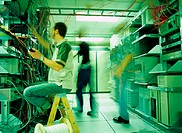 IT technicians working in server room (blurred motion)