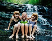 Three girls (6-10) sitting in front of waterfall, smiling, portrait