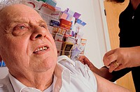 Elderly male patient being immunized with a flu vaccination. NO ADVERTISING USE.