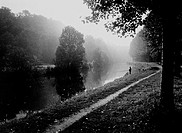 Person fishing from riverbank (B&W)