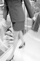 Businesswoman carrying briefcase, mid-section (blurred motion, B&W)