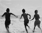 Three Young Boys Running into the Ocean
