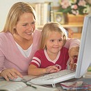 Mother and daughter (3-5) using computer, smiling