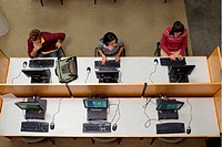 Three college students working in computer lab, overhead view