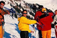 Five people standing, carrying ski pole