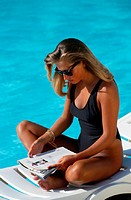Woman reading magazine by the pool