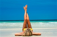 Young woman lying down, leaning her barefeet at beach