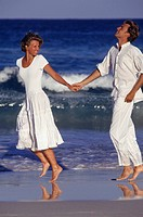 Young couple in white, running along beach