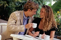 Young couple drinking coffee in garden