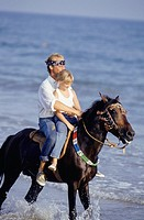 Father and daughter (6-7) riding horse in surf