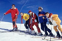Young man and four teenagers (13-14) standing on ski slope