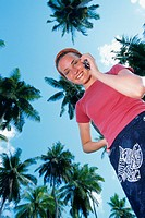 Young woman talking on phone among palm trees, low angle, three quarter length