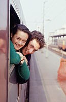 Young couple leaning out of train window, portrait