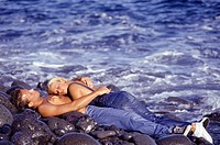 Young couple lying and embracing on rocks at ocean