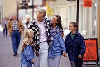 Parents with daughter (8-9) and son (12-13) walking on street