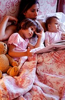 Mother reading to daughter (2-3 years) and baby (6-9 months) in bed