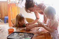 Mother baking with two three year old girls.
