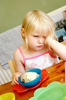 3 year old girl sitting at the table, with food infront of her, looking miserable