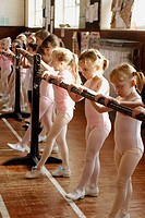 Group of 6 year old girls in ballet class, dressed in pink leotards at a ballet bar