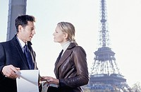 Paris, France, Two young businesspeople talking with clipboard