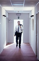 Businessman walking down corridor with jacket over shoulder, front view