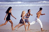 Four young people running on beach, side view