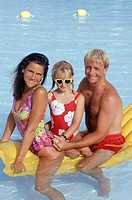 Parents with daughter (6-7) sitting on air mattress in pool, portrait
