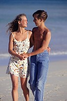 Young couple walking on beach, three quarter length