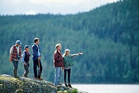 Five people standing on rock by water
