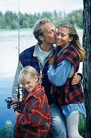 Parents with daughter (8-9) fishing at lake